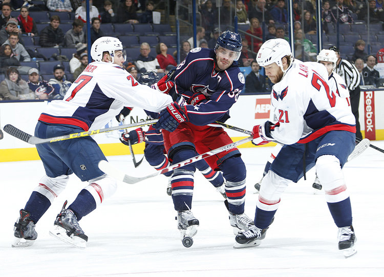 The+Columbus+Blue+Jackets%27+Boone+Jenner+%2838%29+is+sandwiched+by+the+Washington+Capitals%27+Karl+Alzner+%2827%29+and+Brooks+Laich+%2821%29+in+the+third+period+at+Nationwide+Arena.