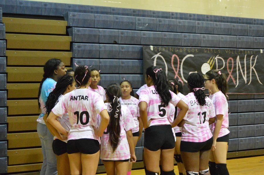 The volleyball team gather in a huddle after their Dig Pink game.