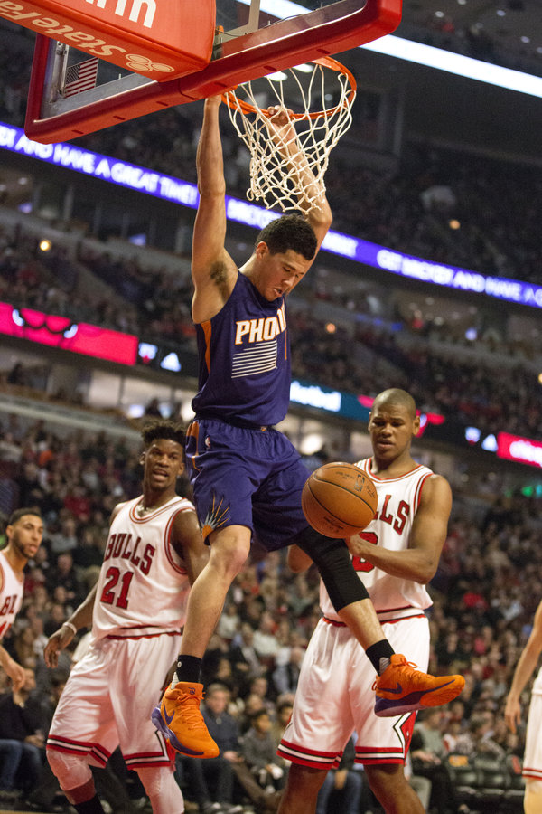 The Phoenix Suns' Devin Booker (1) hangs from the basket after dunking against the Chicago Bulls on Friday, Feb. 24, 2017, at the United Center in Chicago. (Erin Hooley/Chicago Tribune/TNS)