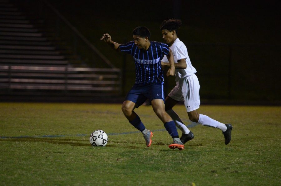 Victor+Giron+of+the+Boys+Varsity+Soccer+team+passes+a+defender.+